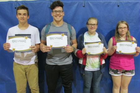 four students with awards for perfect attendance